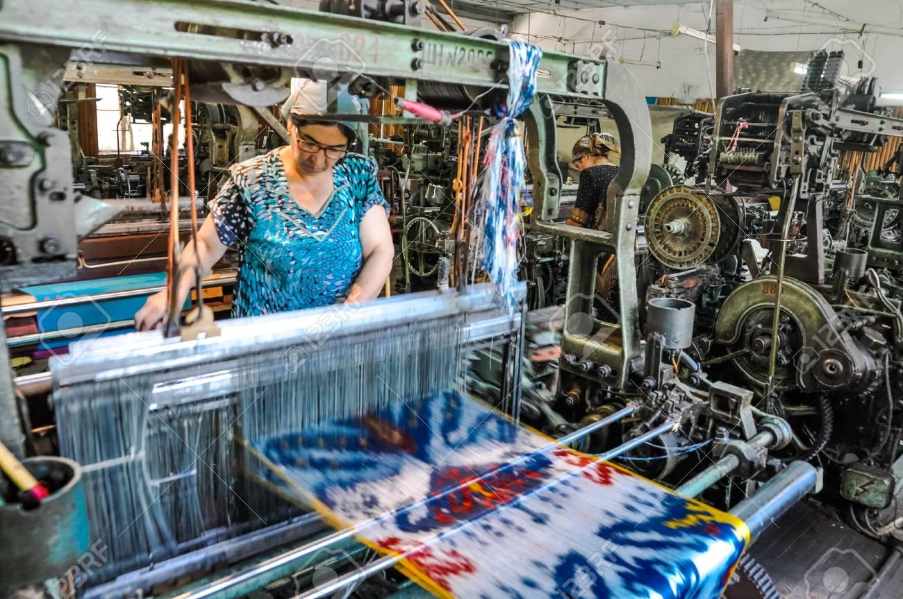 Margilan, Uzbekistan - circa July 2011: Woman works at weaving machine in Uzbekistan's largest traditional silk factory, in Yodgorlik Silk Factory. Documentary editorial.